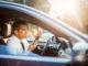 Blick durch die geöffnete Beifahrerscheibe zeigt einen wütenden Autofahrer mit Smartphone in der rechten Hand