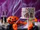 Halloween-Party Tischdeko mit Spinnweben Schokotorte, Totenkopf-Kerzen, Kürbis und Spinnweben Deko im Hintergrund